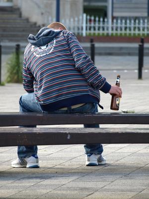 Jugenlicher mit einer Flasche Bier auf einer Parkbank