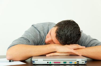 Mann, der sich müde auf seinen Laptop stützt