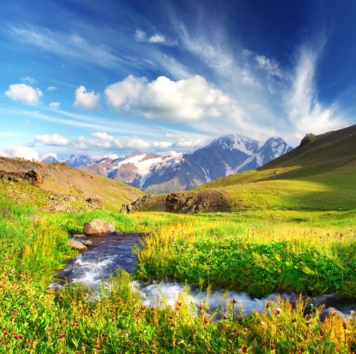 Berge im Hintergrund, grüne Wiesen und ein Bach im Vordergrund
