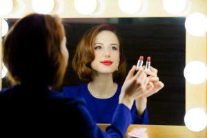 Frau schminkt sich am Hollywoodspiegel