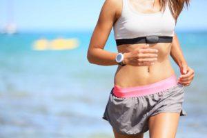 Frau läuft mit Sportuhr mit Brustgurt