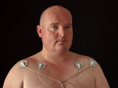 Mann mit Eltroden, die Strom in seinen Körper leiten