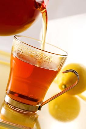 Aus einer Teekanne wird Tee in eine Tasse geschüttet