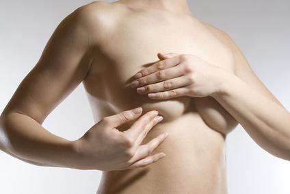 Frau tastet Brust nach Knoten ab