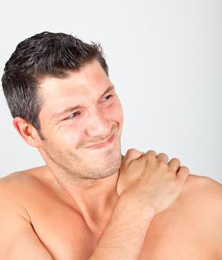 Mann, der sich die Schulter hält und anscheinend Schmerzen hat