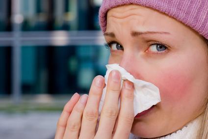 Junge Frau, die sich aufgrund einer Allergie schnäuzt.
