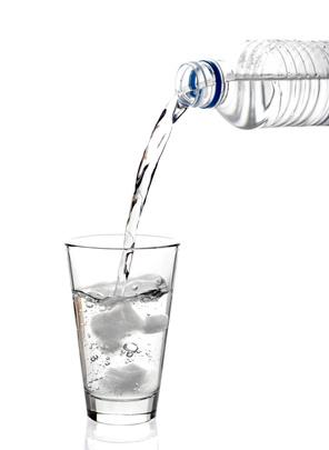 aus einer Wasserflasche wir Wasser in ein Glas geschüttet