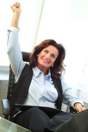 Frau auf Bürostuhl hebt die Hand