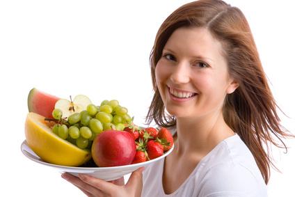 Junge Frau trägt Schüssel mit Obst