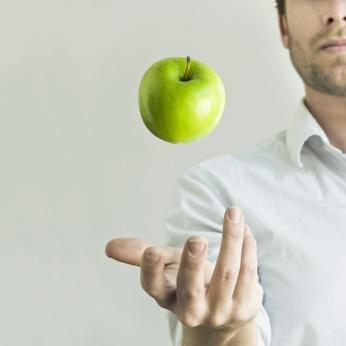 Mann wirft Apfel hoch