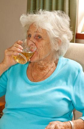 Alte Frau trinkt Alkohol