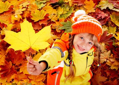 Kind spielt draußen mit Herbstblättern
