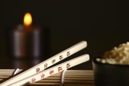 Chinesische Essstäbchen, im Hintergrund Reis