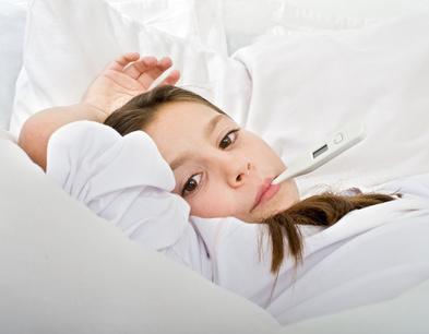 Mädchen liegt mit Fieberthermometer im Bett