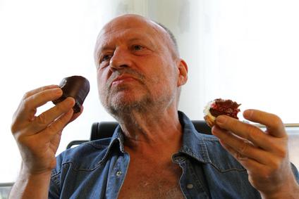 älterer Mann isst süßes