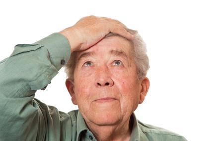 Alter Mann fasst sich an die Stirn
