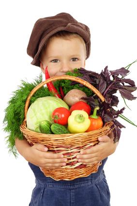 Kind trägt Korb mi Gemüse