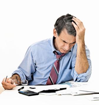 Depressiver, besorgter mann an einem Schreibtisch