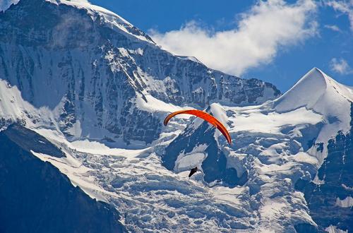 Paragleiter mit roten Schirm. Dahinter schneebedckte Felswände eines Gebirges
